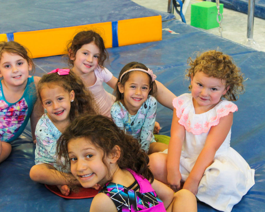 Group of girls sitting on a gymnastics floor mat