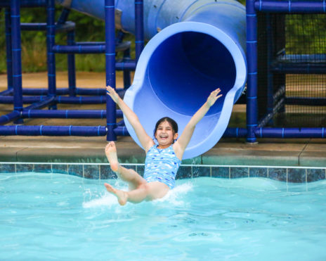 young girl sliding down a water slide into the pool