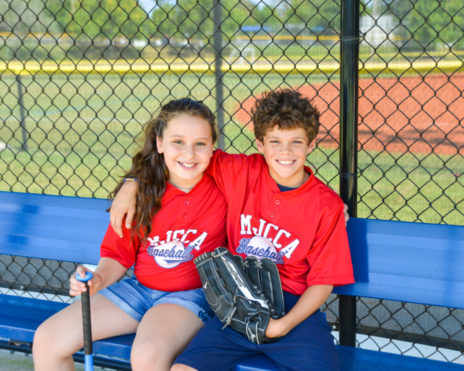 A boy and a girl with baseball bat and glove sitting on bench together