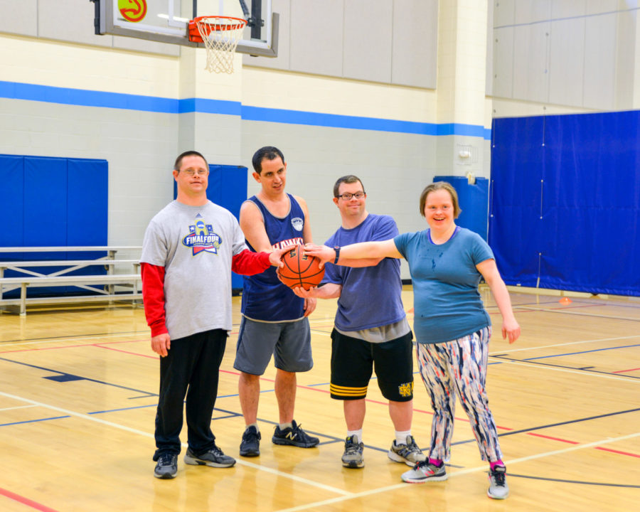 Group of adults on a basketball court holding a basketball