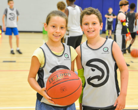 Boy and girl holding a basketball on a basketball court