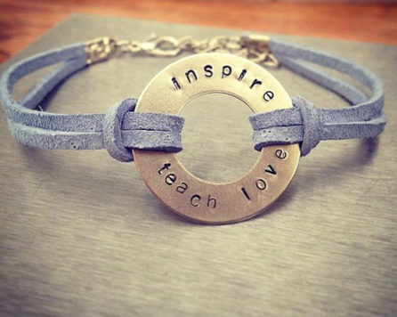 """Handmade bracelet with a pendant in the middle that says """"inspire, teach, love"""""""