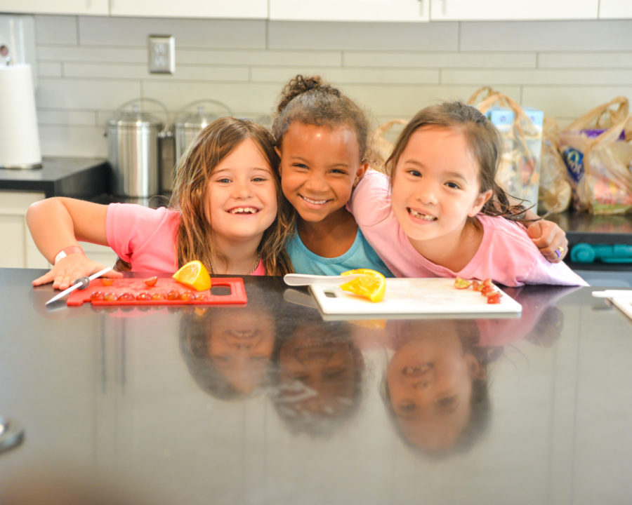 Three girls smiling at a kitchen counter while cooking