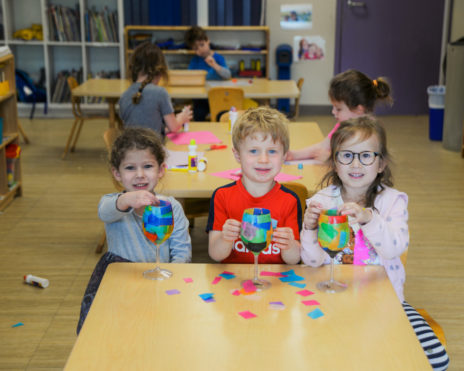 Three preschool kids making crafts
