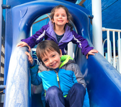 Two kids on a playground slide