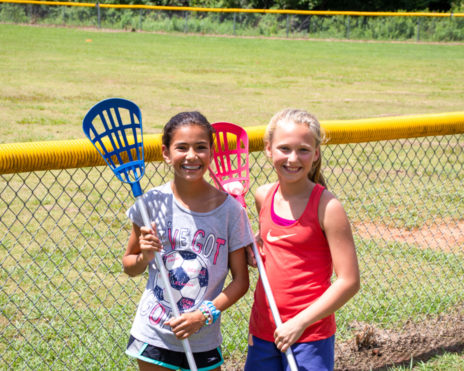 Two girls holding lacrosse sticks