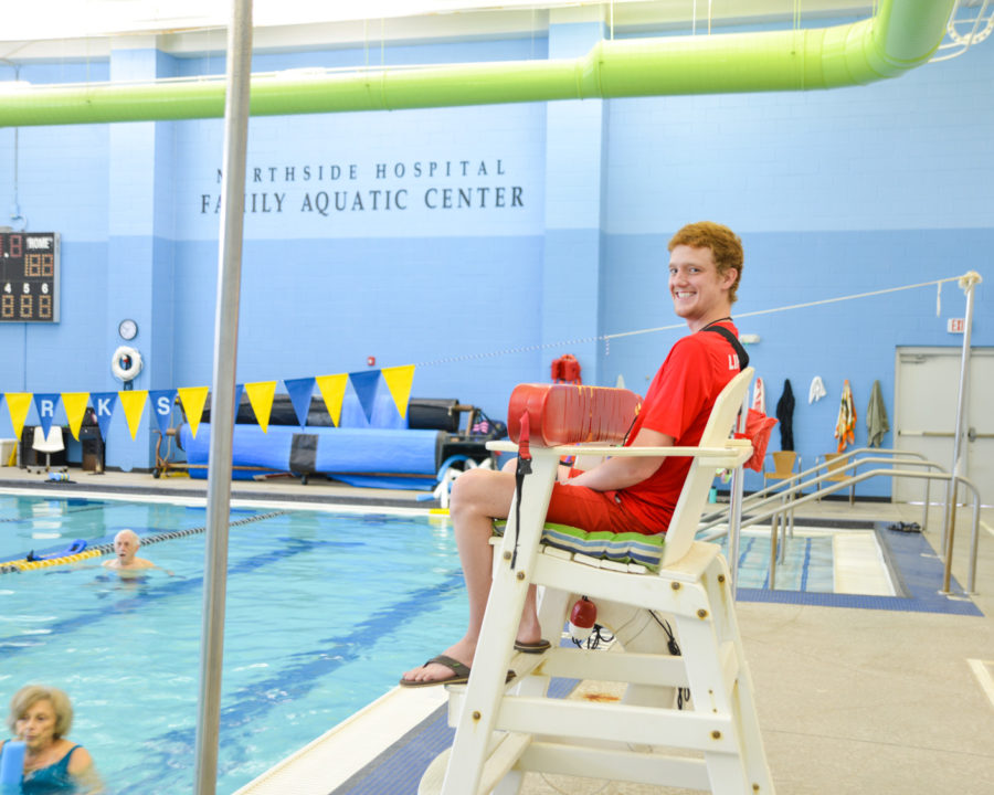 Lifeguard sitting at lifeguard chair at indoor pool