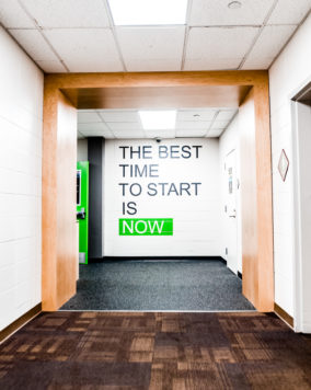 "Entrance to the gym with a wall that has the quote ""the best time to start is now"""