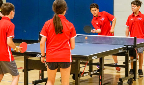 Two teams of two playing table tennis