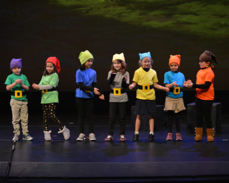 Group of kids dressed up as the seven dwarves on stae