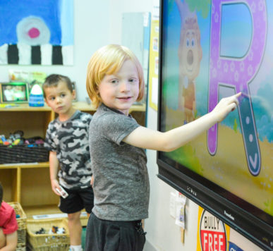 Preschool kids practicing their letters on a screen