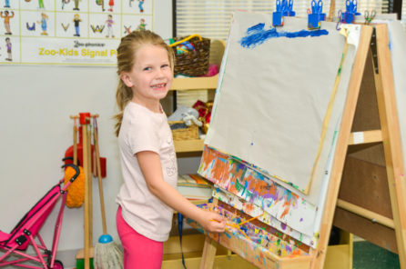 Preschool girl painting on an easel