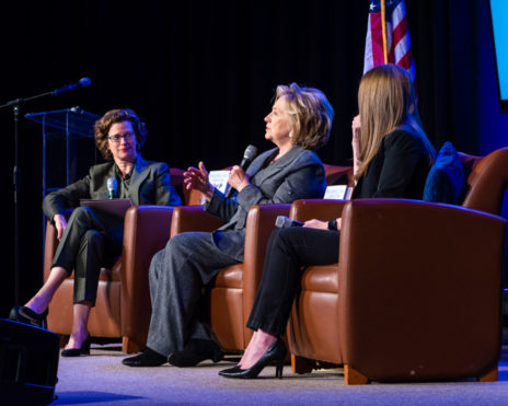 Hilary Clinton speaking on stage with two other women, all sitting in chairs