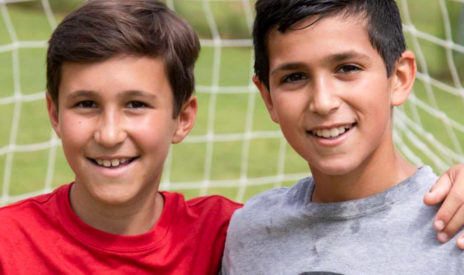 Two boys smiling on the soccer field
