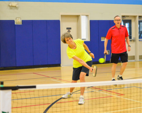 Older adults playing indoor tennis