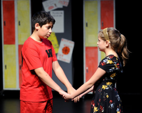 A boy and a girl holding each others hands looking into each others eyes on stage