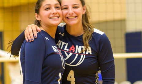 Two volleyball players smiling for a photo