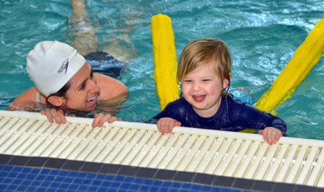 Staff teaching a toddler how to swim