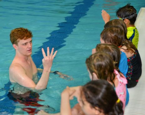 Staff teaching toddlers how to swim
