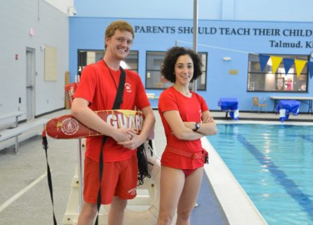 Two lifeguards standing by a pool