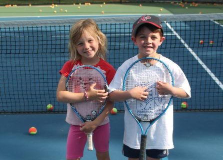 Two young children holding tennis rackets