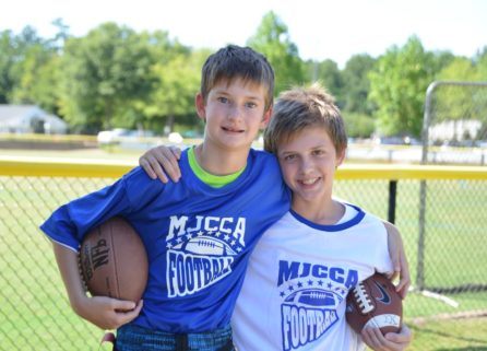 Two youth holding a football