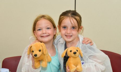 Two girls at summer camp with stuffed animals