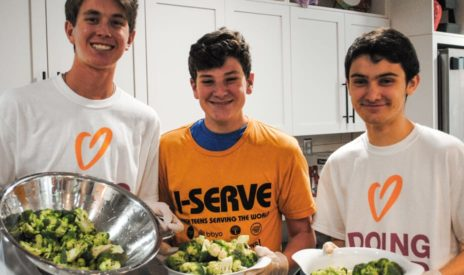 Boys holding bowls of salad at a J-Serve International Day of Service event