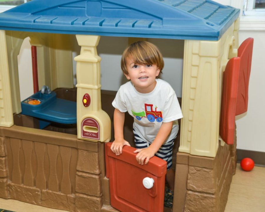 Boy on in a playhouse at the Kid Zone Drop-off Childcare program