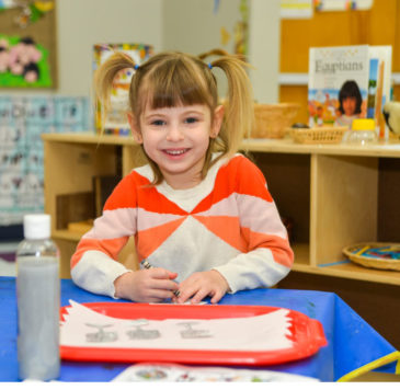 Girl with pigtails at table at MJCCA Schiff School (Sandy Springs)