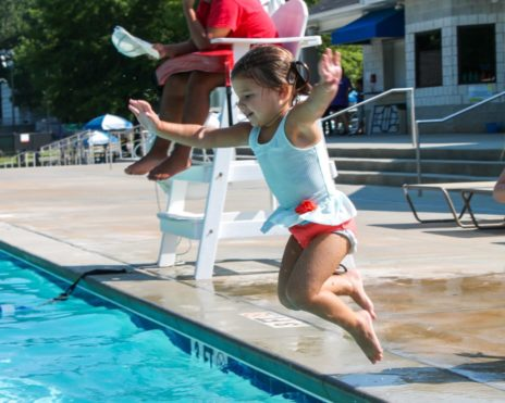 Young child jumping into a pool at Preschool Summer Camp