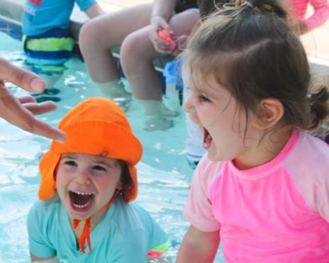Two young children swimming in a pool at the Preschool Summer Camps (Infants-PreK) program