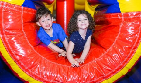 two kids in an inflatable tube at the School's Out Camp program