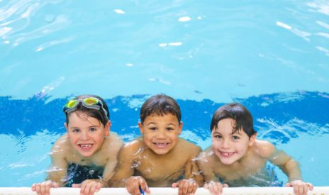 Three boys in the pool at School's Out Camp program