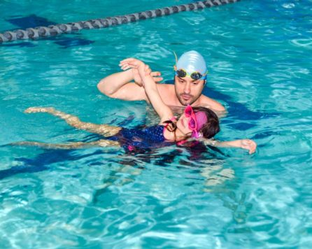 Staff helping a child learn how to freestyle swim