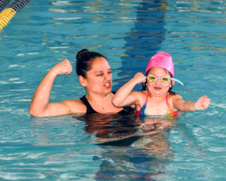 staff and child showing arm muscles in a pool