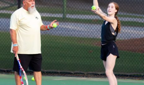 Teen and instructor playing tennis