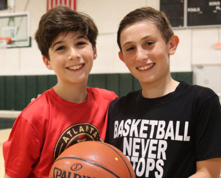 two teens holding a basketball