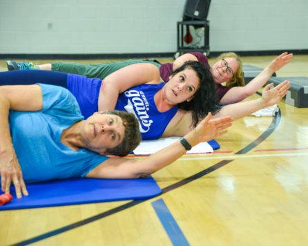 Teens laying on a floor exercising