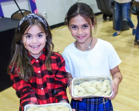 Two girls holding baked goods at a JCC event