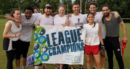 Group of young adults with a League Champions sign