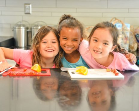 Three young girls at cooking at the arts & culture program
