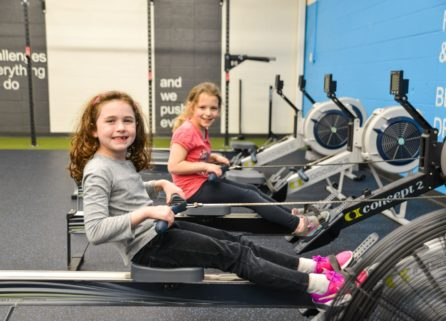Girls at youth fitness on machines